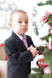 Boy decorate a Christmas tree Royalty Free Stock Image