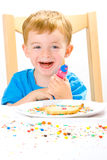 Boy decorating baked biscuits Royalty Free Stock Photos