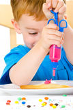 Boy decorating baked biscuits stock photo