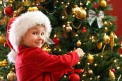 Boy decorating Christmas tree Stock Photos