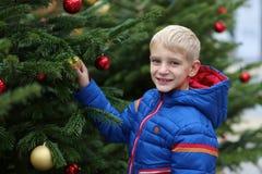 Boy decorating christmas tree Stock Image