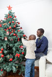 Boy decorating the christmas tree with his father Stock Photography