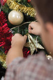 Boy decorating the Christmas tree,shot from behind Royalty Free Stock Image