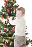 Boy decorating Christmas tree Stock Photography
