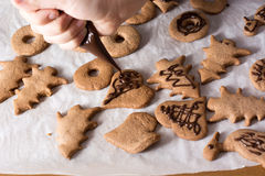 Boy decorating gingerbread cookies with chocolate. Decorating gingerbread cookies with chocolate on the white sheet of paper Stock Images