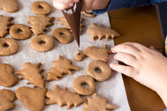 Boy decorating gingerbread cookies with chocolate. Decorating gingerbread cookies with chocolate on the white sheet of paper Stock Photography