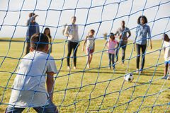 Boy defending goal during a family football game royalty free stock photography