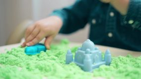 A boy in a denim shirt builds castles and various figures of green kinetic sand stock video footage