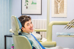 Boy on the dentist chair showing braces. Caucasian teenager with moustache and acne skin sitting on the dentist chair is smiling showing braces Royalty Free Stock Photo