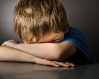 Boy in depression. Sad lonely child on gray background Stock Image
