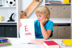 Boy on desk with bad report card. Blond boy on desk with bad report card royalty free stock image