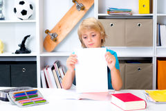 Boy on desk with bad report card. Blond boy on desk with bad report card stock image