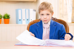 Boy at the desk looking through a folder Stock Image