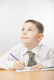 Boy at desk looking up Royalty Free Stock Image