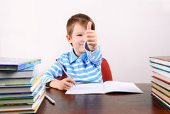 Boy at the desk shows a hand with a thumb up. Cheerful smiling boy sitting at the desk and shows a hand with a thumb up. boy 5 years. on the desk a lot of books Stock Photos