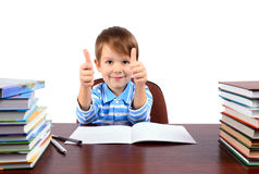 Boy at the desk shows thumbs up. Smiling boy 5 years at the desk shows a hands with a thumbs up. isolated on white background. horizontal Stock Photos
