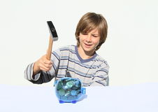 Boy destroying saving pig full of money with hammer Stock Photography