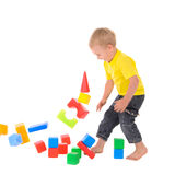 Boy destroys toy building of colored cubes Stock Images