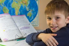 The boy did homework and smiles. The boy did homework and smiles and looks into the frame Royalty Free Stock Image