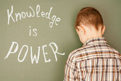 Boy did not learn a lesson. And a message on the board `Knowledge is power Stock Photos