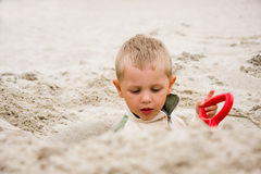 Boy dig in sand on beach Stock Photos
