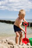 Boy dig in sand on beach Royalty Free Stock Photos