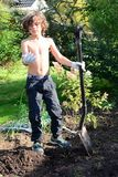 Boy digging after worms in garden. Boy diggin after worms and finds one, happy fishing day, sun is shining in garden Royalty Free Stock Photos