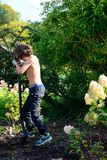 Boy digging after worms in garden. Boy diggin after worms and finds one, happy fishing day, sun is shining in garden Stock Photography
