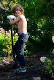 Boy digging after worms in garden. Boy diggin after worms and finds one, happy fishing day, sun is shining in garden Royalty Free Stock Photo