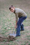 The boy is digging the earth in a park autumn. Person digging in garden Royalty Free Stock Photo