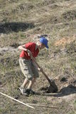 Boy digging in field. A young boy digging a hole in a rough field or hillside Royalty Free Stock Photo