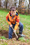 Boy digging in the ground Royalty Free Stock Image