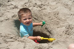 Boy Digging a Hole. Boy digging a deep hole at the beach Stock Photography