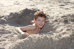 Boy Digging Hole In Sand Royalty Free Stock Photos