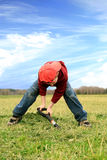 Boy digging on the meadow. Stock Photo