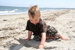Boy digging in the sand. White boy digging in the sand Royalty Free Stock Image