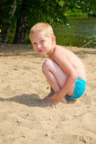 Boy digging sand. A boy plays in the sand by the river royalty free stock photography