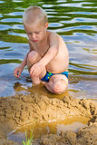 Boy digging sand. A boy plays in the sand by the river Stock Photography