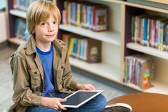 Boy With Digital Tablet In Library Stock Photo