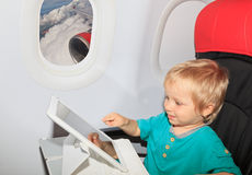 Boy with digital tablet in plane. Little boy with touch pad on plane in flight Royalty Free Stock Images