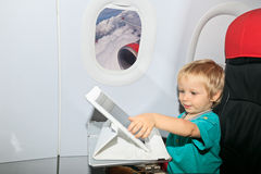 Boy with digital tablet in plane Stock Image