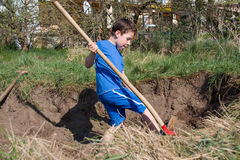 Boy digs a hole Royalty Free Stock Photography