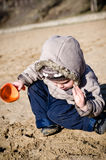 Boy digs in sand. Boy digs a shovel in sand on a beach in the autumn dressed in a jacket Stock Photo