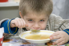 Boy dines. Little boy  of the kindergarten eat soup Stock Photo