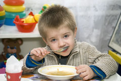 Boy dines. Little boy  of the kindergarten eat soup Royalty Free Stock Images