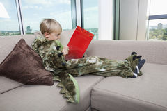 Boy in dinosaur costume reading story book on sofa at home Royalty Free Stock Photos