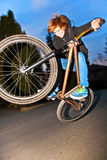 Boy with dirtbike is going airborne. By night royalty free stock image