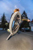 Boy with dirtbike is going airborne. By night Stock Image
