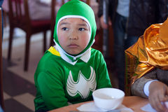 The boy disguise oneself as a batman with green clothes.DA LAT, VIET NAM- OCTOBER 30. Schoolboy disguise oneself as a batman, he wears green clothes, sit at Royalty Free Stock Photography