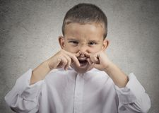 Boy disgust on face pinches nose something stinks. Closeup portrait child boy with disgust on face pinches his nose something stinks bad smell situation isolated royalty free stock photo